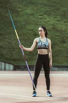 Vrouwelijke speerwerper die weg houdend een speer kijken