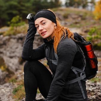 Vrouwelijke sportieve jogger die een pauze middellang schot neemt