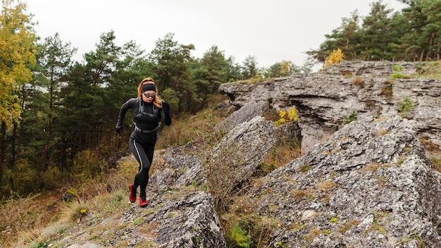 Vrouwelijke sportieve jogger die op stenen afstandsschot loopt