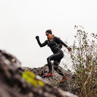Vrouwelijke sportieve jogger die op stenen loopt