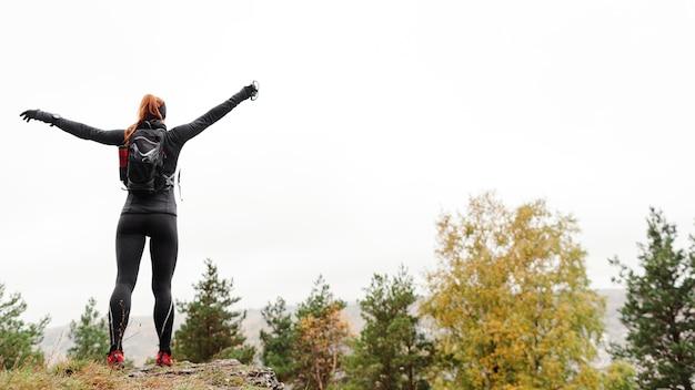 Vrouwelijke sportieve jogger die zich lang shot van achteren uitstrekt