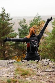 Vrouwelijke sportieve jogger die zich uitstrekt in de natuur