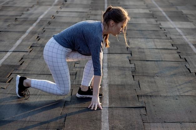 Vrouwelijke sprinter die op het begin op een luchthavenbaan wacht