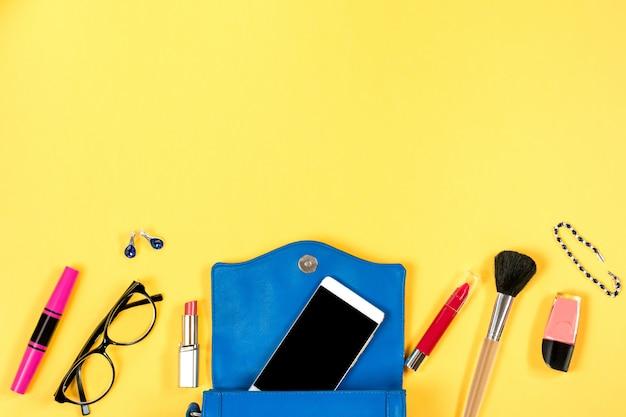 Vrouwelijke spullen op heldere gele achtergrond, bovenaanzicht