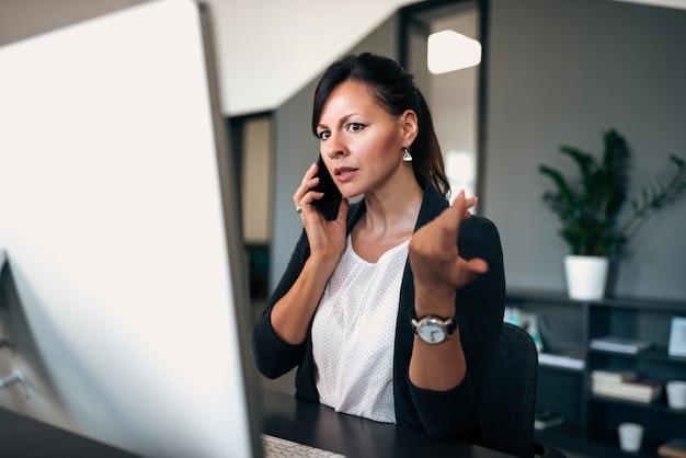 Vrouwelijke stafmedewerker die het computerscherm bekijkt en ernstig gesprek op de telefoon heeft.