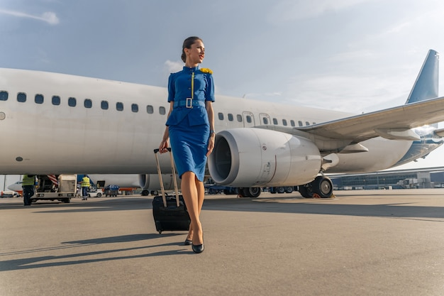 Vrouwelijke stewardess wandelen met zwarte koffer
