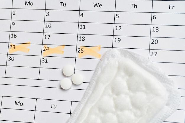 Vrouwelijke strip op kalender met datummarkeringen en hormonale pillen