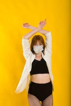 Vrouwelijke stripdanser in gele studio met beschermend masker van covid, zwarte bodysuit