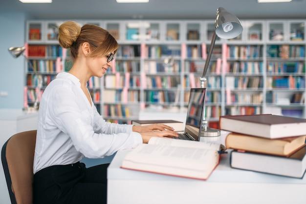 Vrouwelijke student aan laptop in universiteitsbibliotheek.