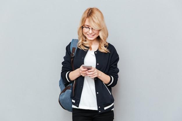 Vrouwelijke student bericht schrijven op smartphone