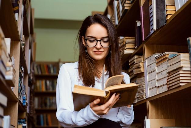 Vrouwelijke student bij de bibliotheek die een boek leest