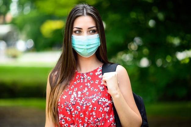 Vrouwelijke student buiten lopen in het park en het dragen van een masker om zichzelf te beschermen tegen coronavirus