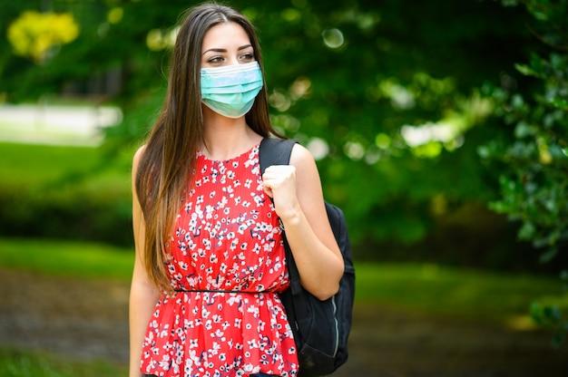 Vrouwelijke student die buiten in het park loopt en een masker draagt om zich tegen coronavirus te beschermen