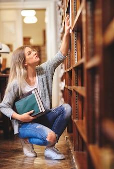 Vrouwelijke student die een boek in bibliotheek zoekt