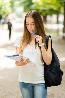 Vrouwelijke student die een boek leest openlucht