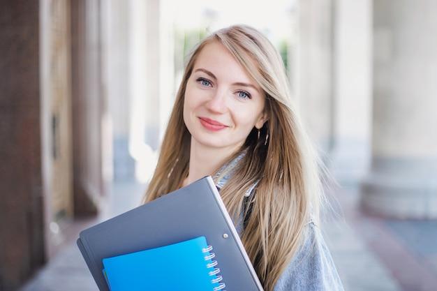 Vrouwelijke student die een notitieboekjemappen houdt en tegen de achtergrond van de universiteit glimlacht