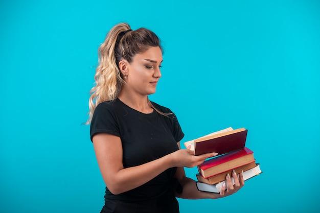 Vrouwelijke student die een zware voorraad boeken vasthoudt en er een opent.