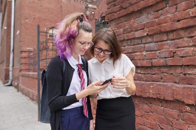 Vrouwelijke student die en met vrouwenleraar loopt spreekt
