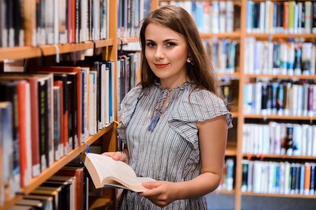 Vrouwelijke student die in het boek van de bibliotheeklezing de camera bekijken