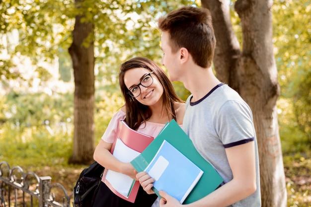 Vrouwelijke student die in liefde een knappe klasgenoot in het park bekijkt, die met hem flirt