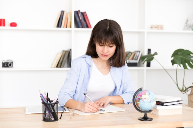 Vrouwelijke student die in notitieboekje schrijft