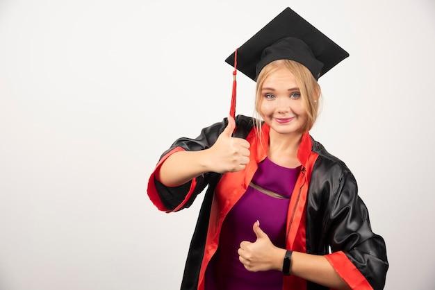 Vrouwelijke student die in toga duimen op wit maakt.