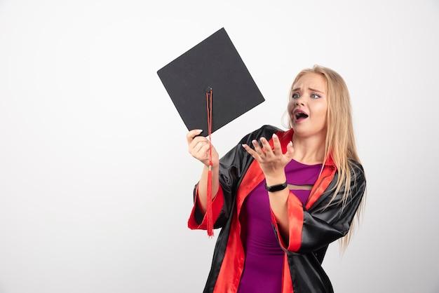 Vrouwelijke student die in toga geschokt op witte achtergrond kijkt. hoge kwaliteit foto