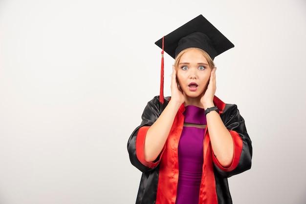 Vrouwelijke student die in toga haar gezicht op wit houdt.
