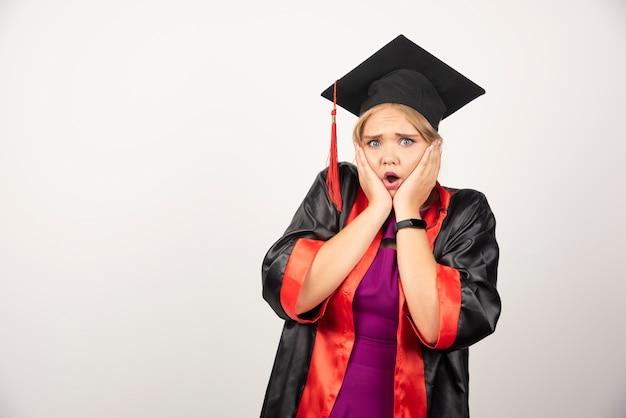 Vrouwelijke student die in toga haar gezicht op witte muur houdt.