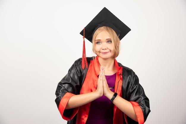 Vrouwelijke student die in toga handgebaar op wit maakt.