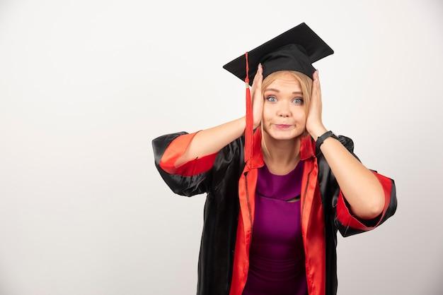 Vrouwelijke student die in toga verrast op wit kijkt.