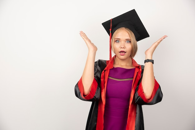 Vrouwelijke student die in toga verrast op witte muur kijkt.