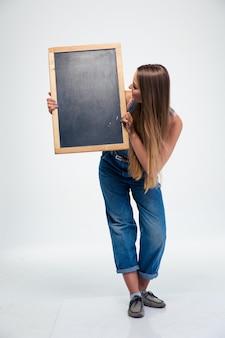 Vrouwelijke student die leeg bord houdt