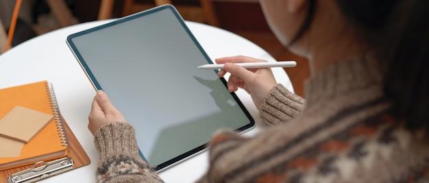 Vrouwelijke student die opdracht met verticale modeltablet en kantoorbehoeften op koffietafel doet