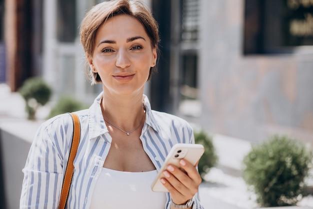 Vrouwelijke student die telefoon buiten de straat gebruikt