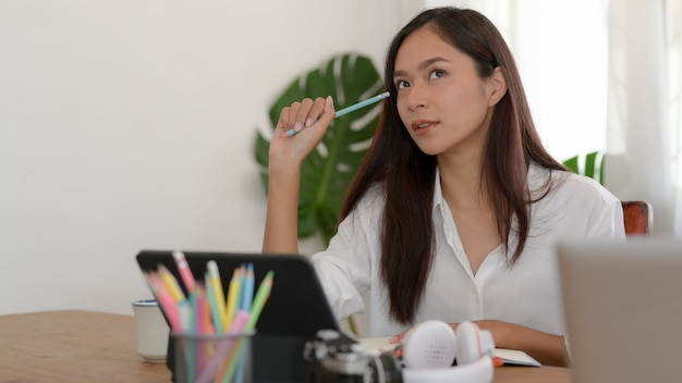 Vrouwelijke student die terwijl het doen van opdracht met digitale tablet en kantoorbehoeften op lijst denken