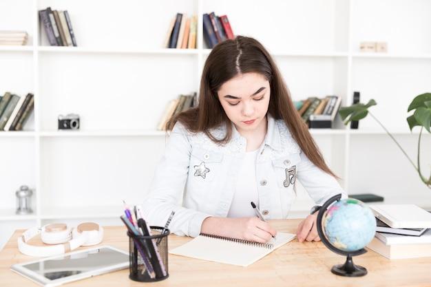 Vrouwelijke student die thuiswerk doet