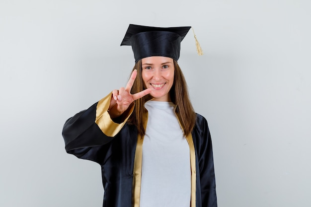 Vrouwelijke student die v-teken in graduatietoga toont en vrolijk, vooraanzicht kijkt.