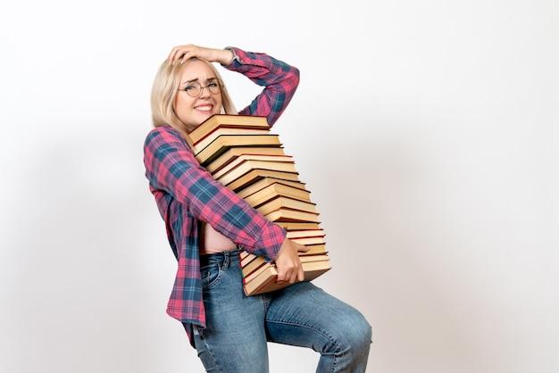 Vrouwelijke student die verschillende zware boeken over licht wit houdt