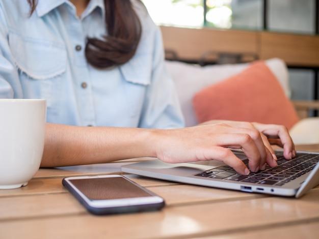 Vrouwelijke student gebruikt toetsenbord om op de computer te typen