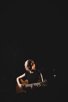 Vrouwelijke student gitaarspelen