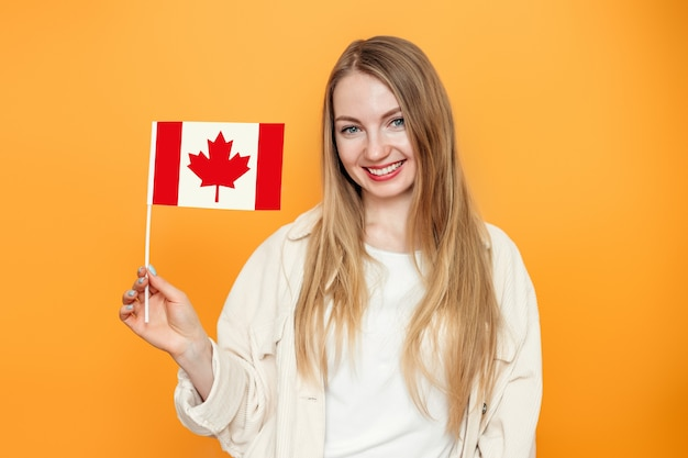 Vrouwelijke student glimlachend en met een kleine vlag van canada
