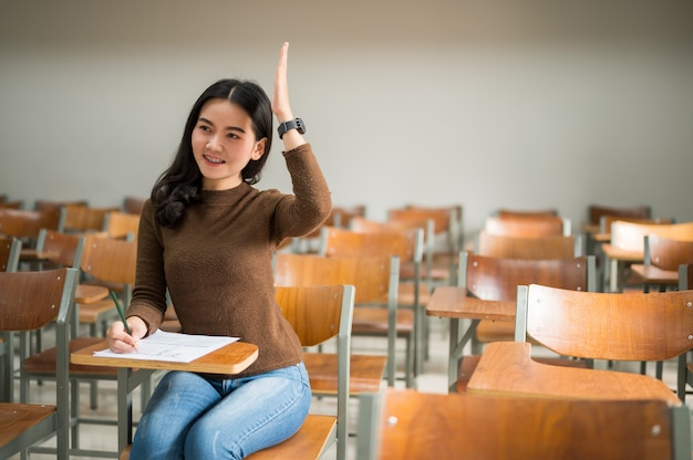 Vrouwelijke student heft handen op en vraagt leraren in het universitaire klaslokaal