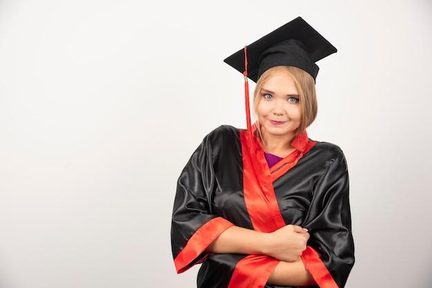 Vrouwelijke student in toga die zich op witte achtergrond bevindt. hoge kwaliteit foto