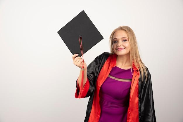 Vrouwelijke student in toga die zich op witte muur bevindt.