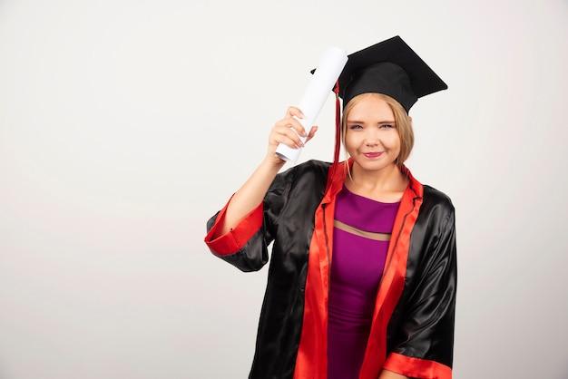Vrouwelijke student in toga met diploma op wit.