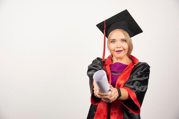Vrouwelijke student in toga ontving diploma op wit.