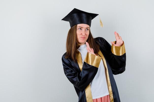 Vrouwelijke student in toga, vrijetijdskleding die stopgebaar toont en bang, vooraanzicht kijkt.