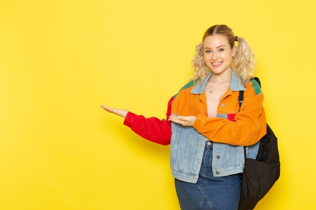 Vrouwelijke student jong in moderne kleding gewoon poseren met een glimlach op geel