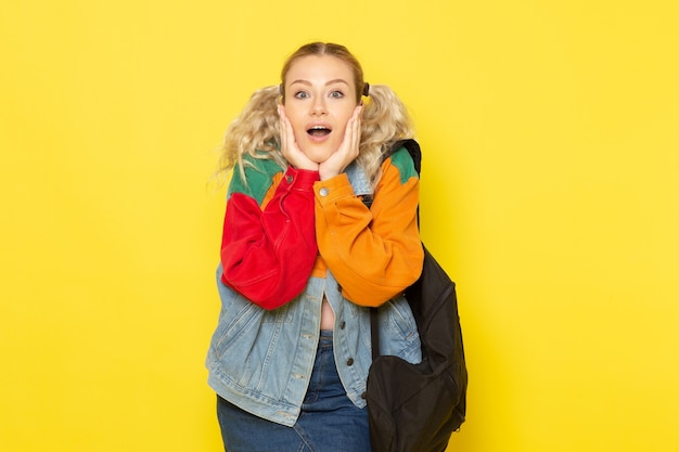 Vrouwelijke student jong in moderne kleding gewoon poseren met verbaasde uitdrukking op geel